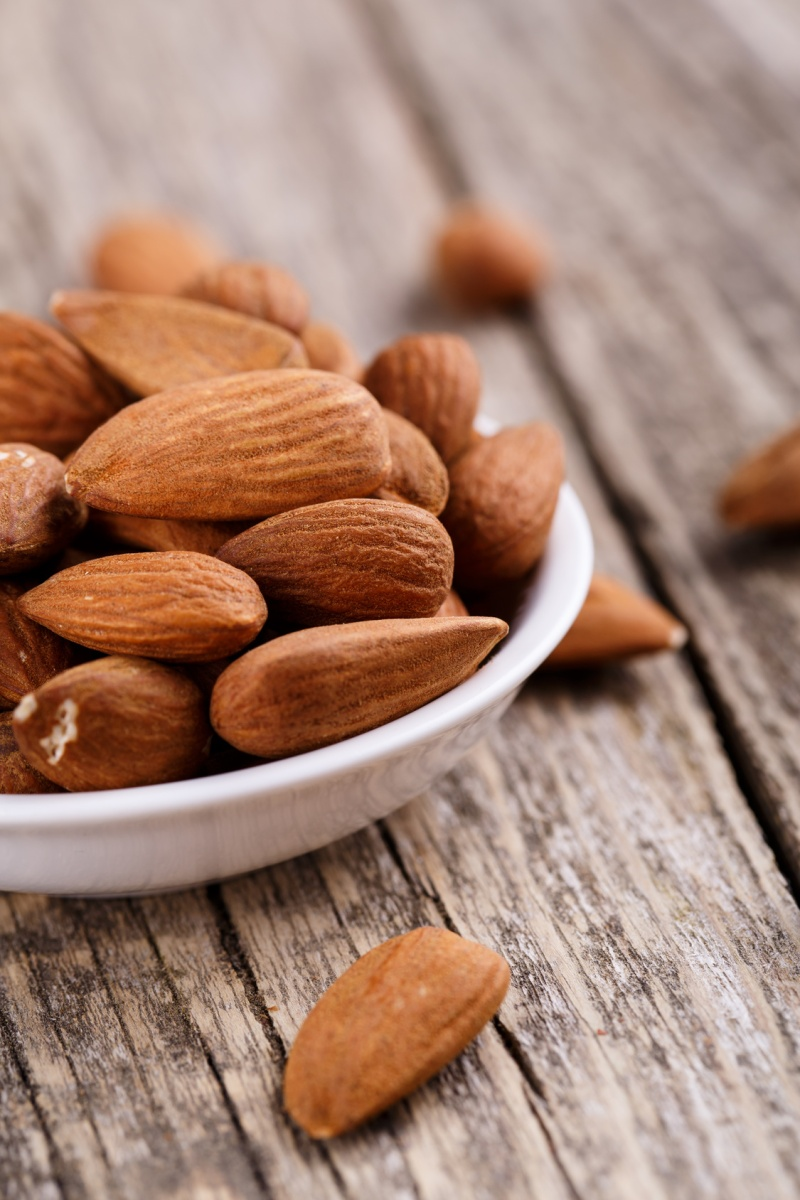 Almonds on a plate on a wooden background.