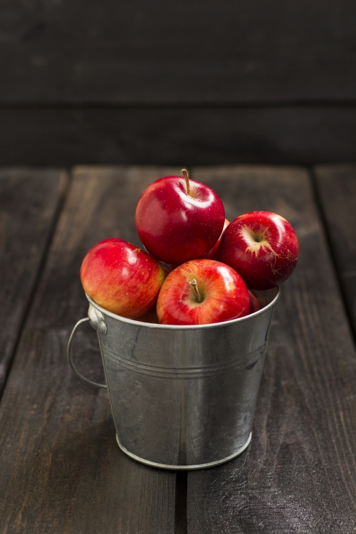 Crop of red apples in metal bucket on a dark wooden background