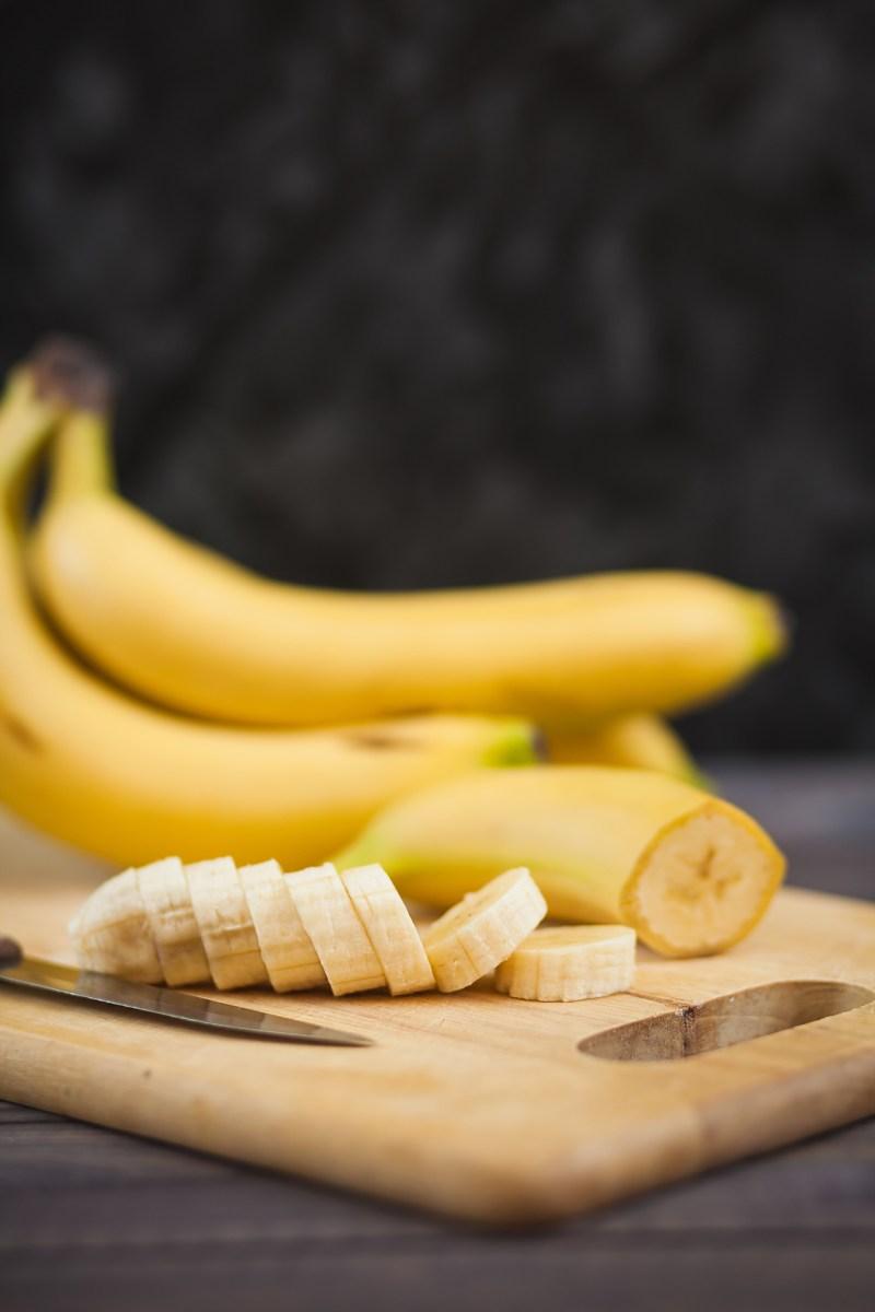 sliced banana with a knife on board
