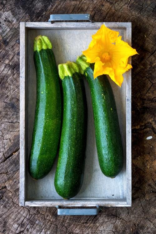 Fresh organic zucchini on wooden background