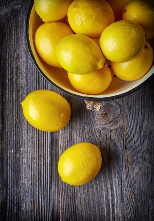 fresh ripe lemons on wooden table, top view