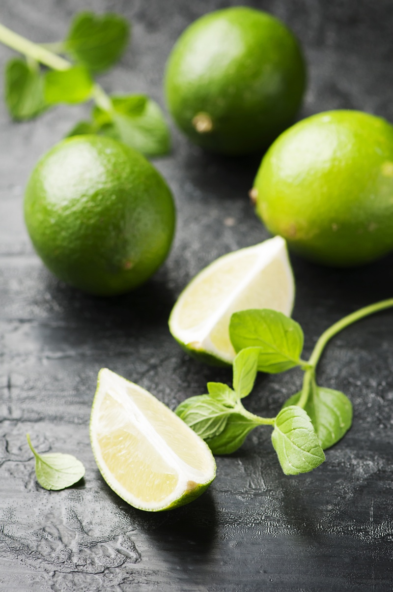 Fresh lime and mint on the black table, selective focus