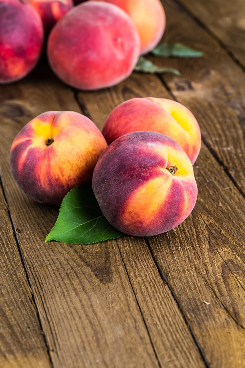 fresh peaches on wood background