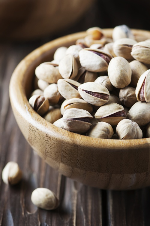 Salt pistachio nuts in the wooden bowl, selective focus