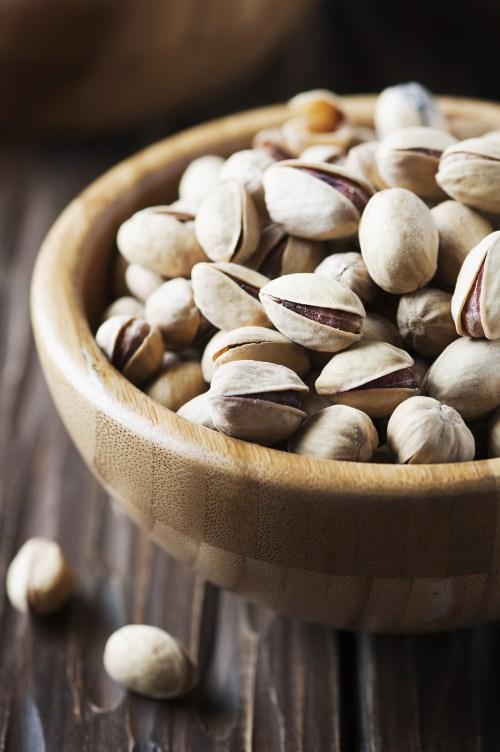 Salt pistachio nuts in the wooden bowl, selective focus