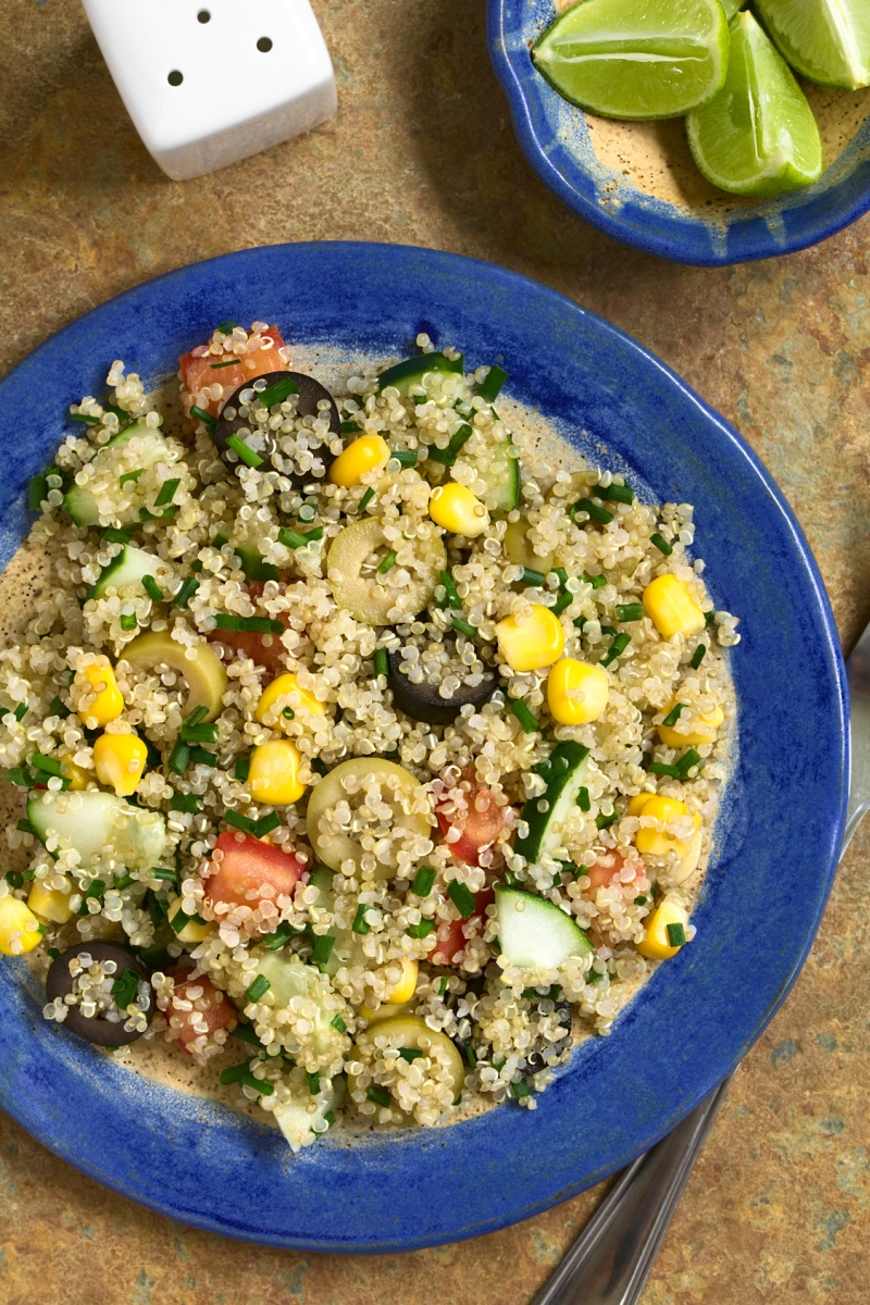 Quinoa salad with sweet corn, olive, tomato, cucumber and chives on plate, photographed overhead on slate with natural light