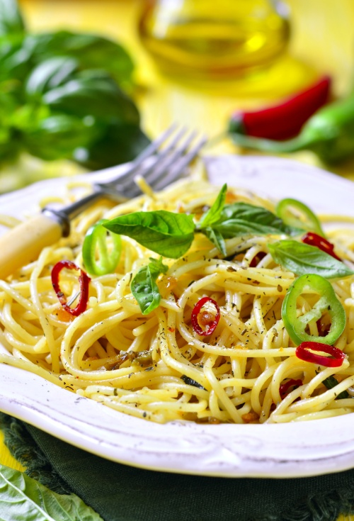 Spaghetti with chili,garlic and basil on yellow wooden table.