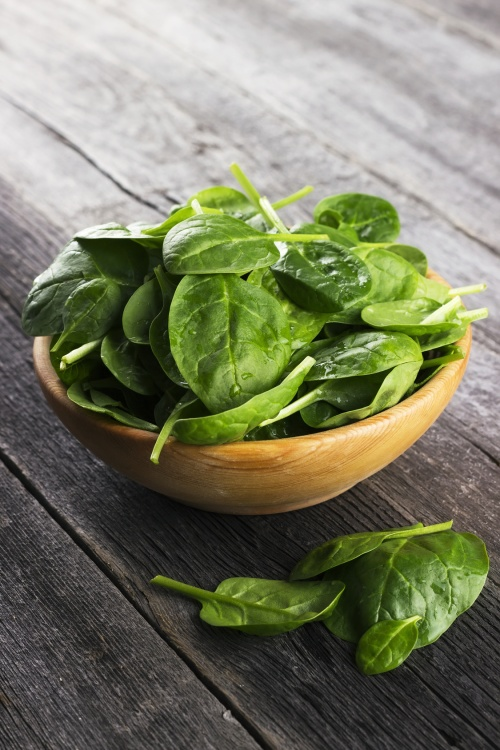 Spinach leaves in bowl on dark wooden background