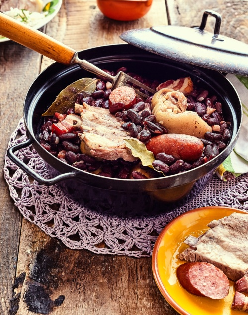 High Angle Close Up View of Traditional Brazilian Stew with Beans and Variety of Meats Served in Black Metal Pot on Doily and Rustic Wooden Table Surrounded with Garnishes