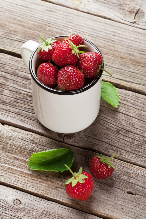 Fresh garden strawberry in cup on wooden table