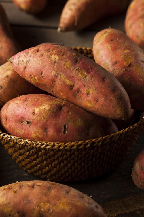 Organic Raw Sweet Potatoes on a Background