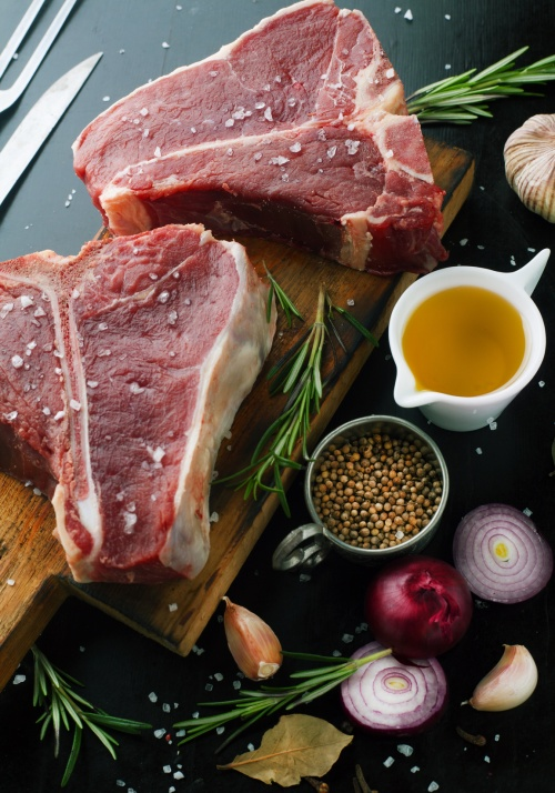 Raw meat t-bone steak with herbs, spices, garlic and rosemary on a dark background