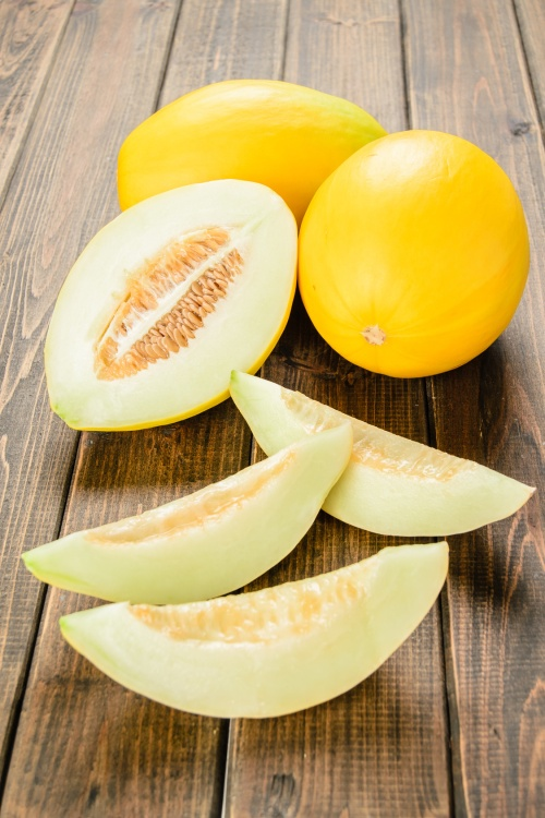 yellow melon slices on the wooden board.