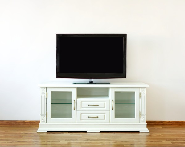 Large widescreen TV set on the white dresser in a bright room.