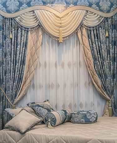Luxury bilateral curtains with floral ornaments, pelmet and pillows on the bed. Design in the bedroom.